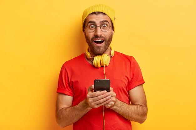 Изолированный снимок возбужденного удивленного мужчины, шокированного получением потрясающего видео от друга, просматривает веб-страницу на смартфоне