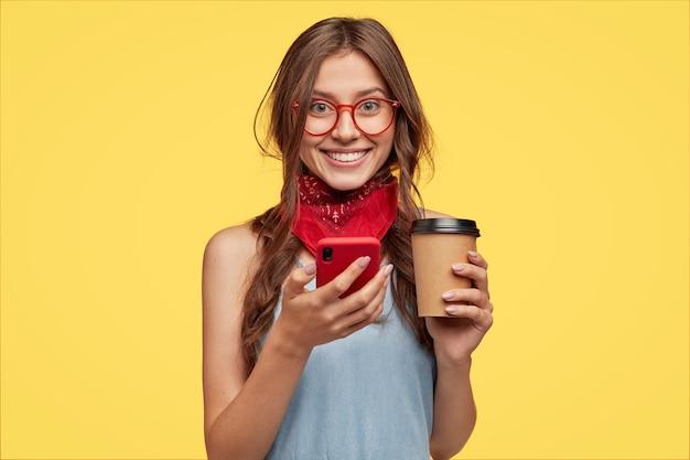 Изолированный снимок симпатичного улыбающегося мальчика, находящегося в приподнятом настроении, пьет кофе на вынос