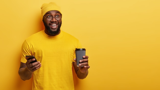 좋은 분위기에서 행복한 아프리카 미국 십대의 격리 된 샷, 인터넷에서 이메일 상자를 확인하고, 현대 가제트를 사용하고, 테이크 아웃 커피를 마시고, 긍정적으로 미소를 짓고, 노란색 벽 위에 포즈를 취합니다. 여가 시간