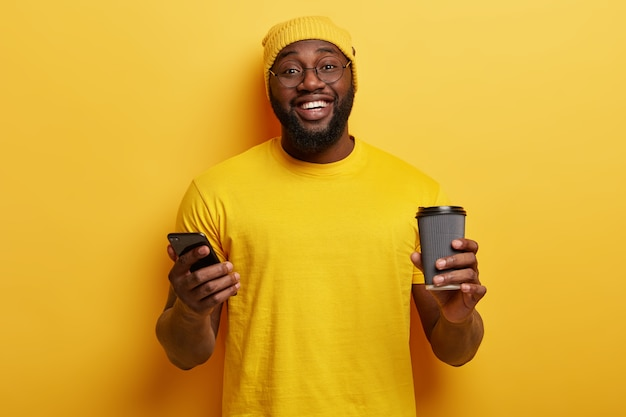 黄色い服を着た幸せな黒人男性の孤立したショット、メッセージを入力し、スマートフォンで新しいアプリケーションをダウンロードし、使い捨てカップからコーヒーを楽しんで、歯を見せる笑顔、白い歯、厚い剛毛を持っています。