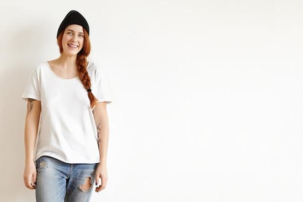 白い壁でポーズ、三つ編みで生姜髪を着て幸せな女の子の分離ショット
