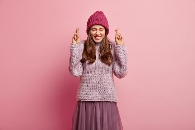 행복하게 기쁘게 생각하는 유럽 여성의 고립 된 샷은 행운을 믿고, 즐거움에 눈을 감고, 넓게 미소를 짓고, 니트 점퍼, 스커트 및 모자를 쓰고, 장밋빛 벽 위에 포즈를 취하고, 여전히 행운을 기대합니다.