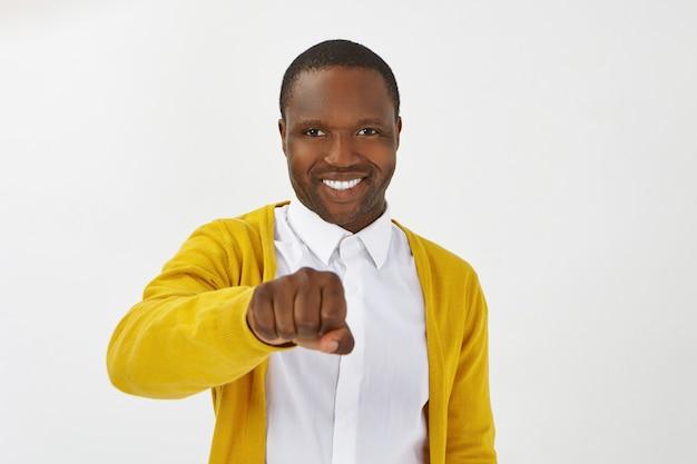 スタイリッシュな服を着てポーズをとって、広く笑って、彼の前にくいしばられた握りこぶしを持って、あなたに挨拶しながらナックルをぶつける準備ができている幸せなポジティブな若いアフリカ系アメリカ人男性の孤立したショット