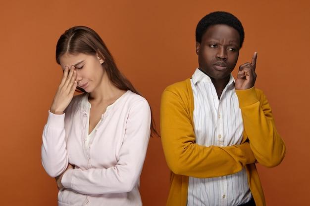 一緒に働いている2人の同僚の異人種間のチームの孤立したショット、何かを思い出そうとしている、彼らの顔に手をつないで、思慮深い表情をして、いくつかの問題を心配している