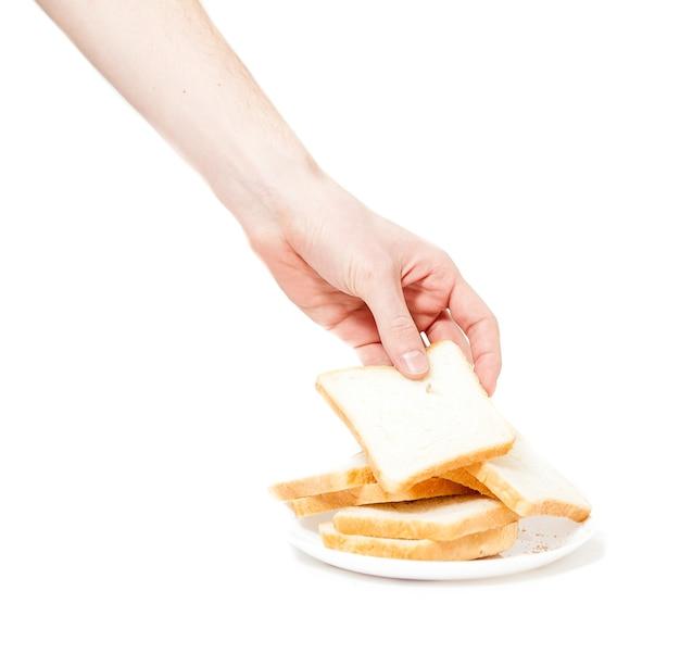 トースト用のパンの切れ端を付ける男性の手の孤立したショット