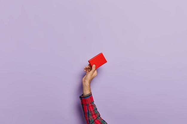 アクセサリーのための空の小さな赤い紙箱と男の手の分離ショット