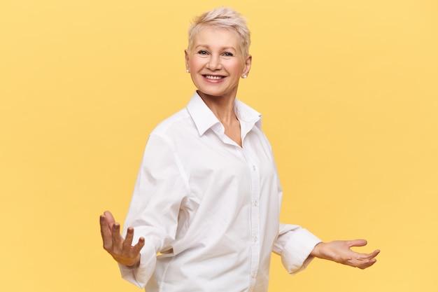 手を大きく広げて幸せそうに笑って、やる気を起こさせるスピーチを与え、従業員を元気づけ、自信を表現する彼女の姿勢で白いシャツを着た大喜びの成功した成熟した女性の上司の孤立したショット