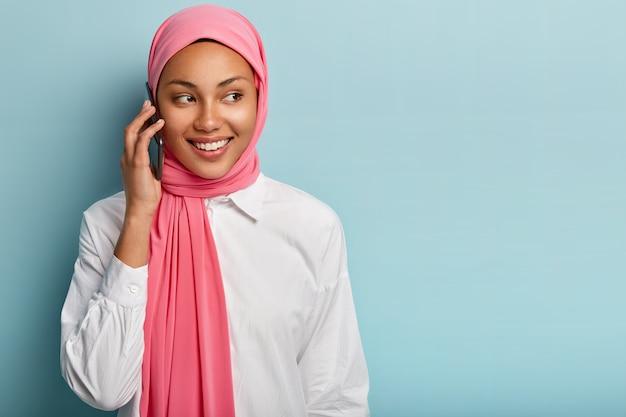 유쾌한 여성 모델의 고립 된 샷은 현대 휴대 전화를 통해 말하고, 누군가와 이야기하고, 진심으로 미소를 짓고, 멀리 집중하고, 빈 공간이있는 파란색 벽에 서서, 이슬람 옷을 입습니다.