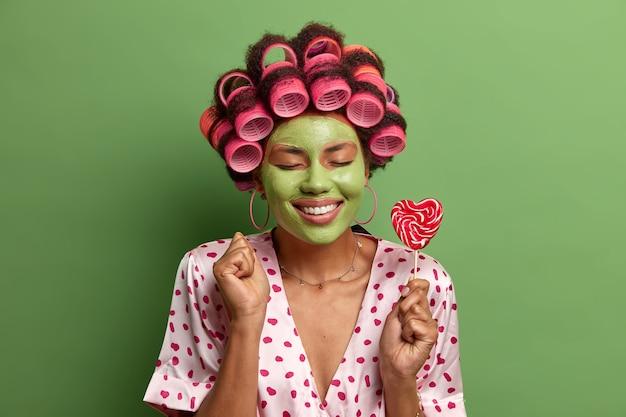 目を閉じて喜んでいる民族の女性の孤立したショットは、喜んで拳を握り締め、ヘアカーラー、美容マスクを身に着け、歯を見せる笑顔、棒にロリポップを保持し、カジュアルな家庭服を着ています