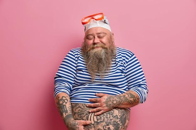 Изолированный снимок пухлого бородатого мужчины, держащего свой толстый татуированный живот, закрывает глаза с удовлетворением, одетый в маленькую матросскую рубашку, резиновую шапочку и очки, увлекается подводным плаванием в летнее время