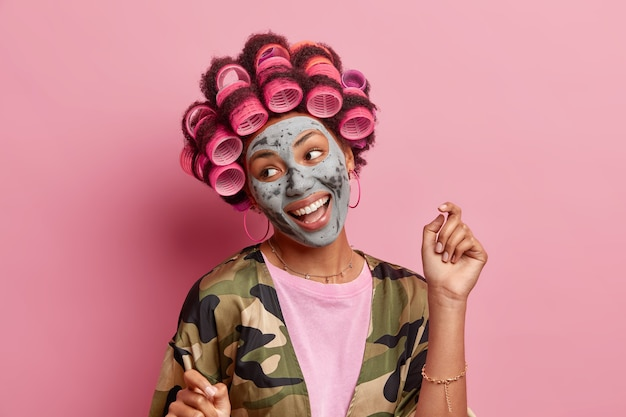 ポジティブな女性の孤立したショットは脇に微笑み、腕を大きく上げ、ヘアローラーを当てる 国産ローブを着た美容マスクは特別な機会に備える 室内で美しいモデルを見たい