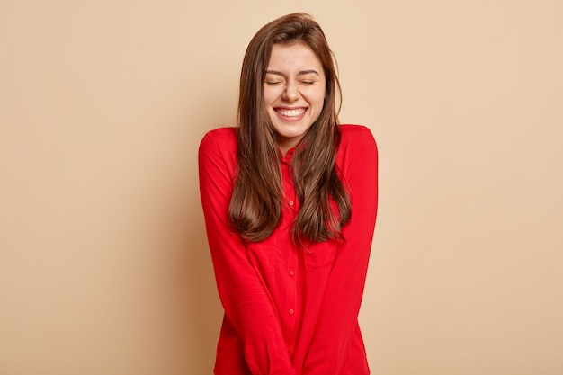 ポジティブな若いヨーロッパの女性の孤立したショットは、楽しさと喜びを感じ、目を閉じて、広く笑顔で、赤い服を着て、茶色の壁に孤立しています。人、感情の概念