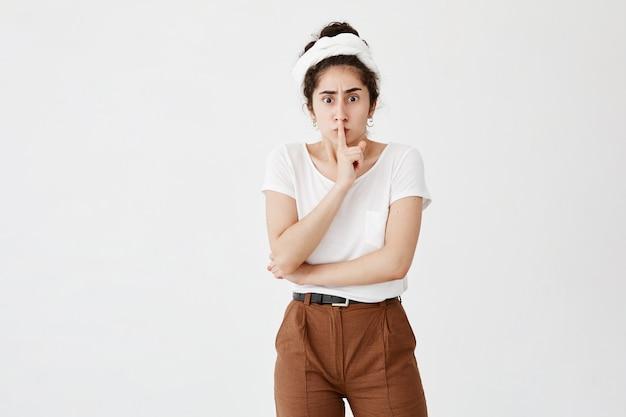 大きなノイズに悩まされている白いtシャツに身を包んだかなり怒っている暗い髪の女性の孤立したショットは、唇に人差し指を保ち、静寂と平和を要求します。静けさ、話をやめてください