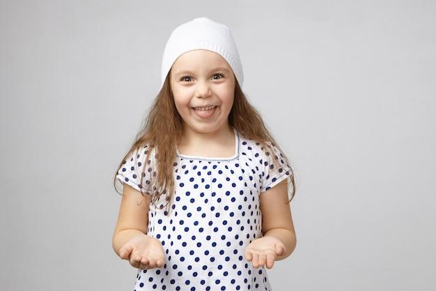 スタジオでポーズをとってかわいい女の子の点線のトップと白い帽子の孤立したショット