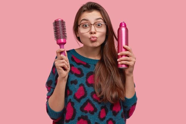 예쁜 여자의 고립 된 샷은 mwah를주고, 입술을 접고, 머리카락을 오래 돌보고, 빗과 헤어 스프레이를 들고, 큰 광학 안경을 착용합니다.