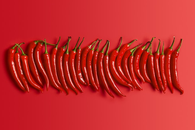 味付けのための緑の茎と光沢のある皮を持つ赤唐辛子の孤立したショット。メキシコのシンボル。スパイシーな商品のコレクション。セレクティブフォーカス。健康的な料理のコンセプト。新鮮な野菜