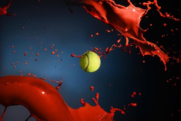 赤いペンキのスプラッシュとテニスボールの分離ショット