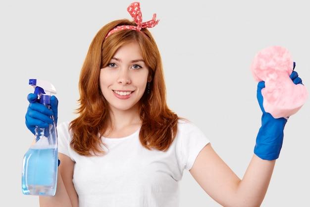満足している女性用務員の孤立したショットは、スプレーとスポンジを保持し、ヘッドバンド、白いtシャツ、保護ゴム手袋を着用し、掃除の準備ができて、屋内に立っています。家事と衛生のコンセプト