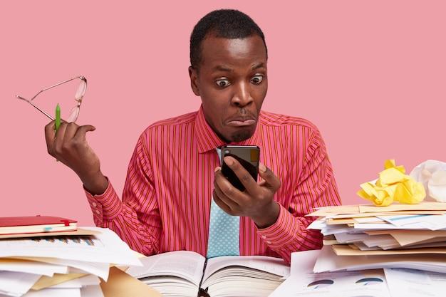 Изолированный снимок шокированного темнокожего парня в официальной одежде, получающего электронное письмо с плохими новостями от сотрудника, смотрит на смартфон с ошибочными глазами