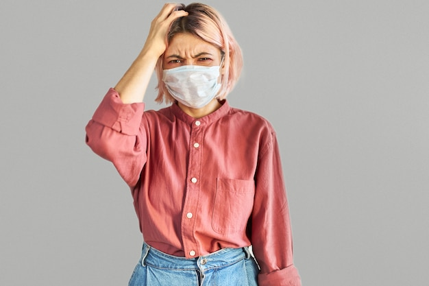 コロナウイルスとインフルエンザの発生時に公共の混雑した場所でフェイスマスクを使用して欲求不満の表情をしているピンクがかった髪の学生の女の子の孤立したショット。ウイルス、病気、予防と保護の概念