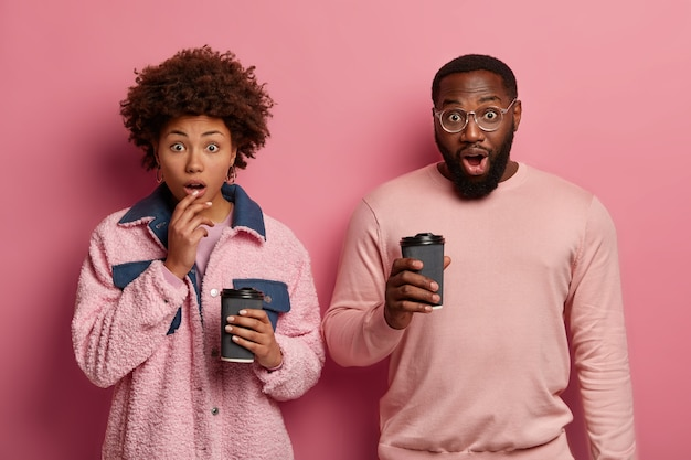 Изолированный снимок ошеломленных темнокожих молодых женщин и мужчин, пьющих кофе на вынос, с шокированными выражениями лиц, слышащих невероятные новости