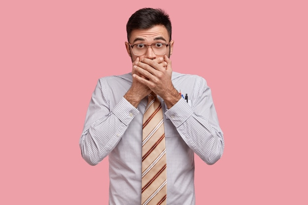 愚かなハンサムな起業家の孤立したショットが口を覆い、言葉を失い、秘密を隠し、衝撃的なニュースに驚いた