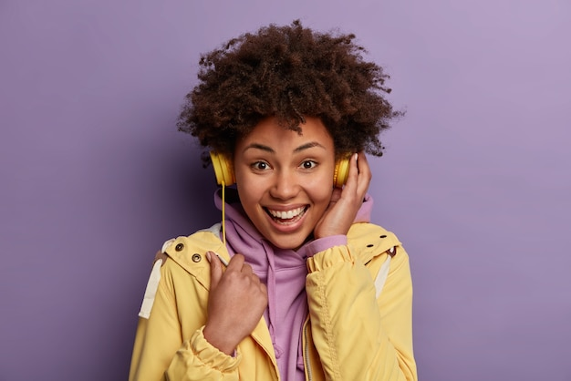 Isolated shot of optimistic curly hipster girl enjoys positive melody in electronic headphones, listens music via modern headset