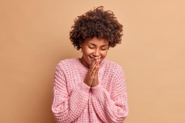 Colpo isolato di donna felicissima non riesce a smettere di ridere di aneddoto divertente tiene i palmi premuti insieme sorride con gli occhi chiusi vestiti con un maglione invernale isolato sopra il muro beige