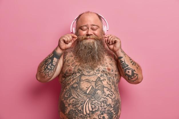 Colpo isolato di uomo barbuto in sovrappeso arriccia i baffi, chiude gli occhi, ascolta le canzoni preferite in cuffia, ha trovato una stazione musicale o un podcast divertente, ha tatuato la pancia nuda, modelli contro il muro roseo