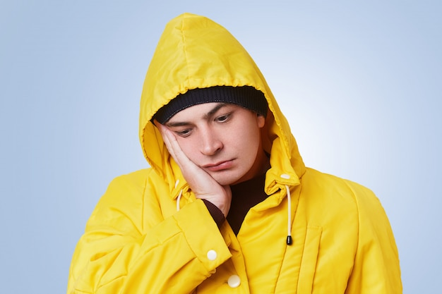 Isolated shot of pensive thoughtful man looks unhappily down, has toothache, keeps hand on cheek, wears yellow anorak with hood. upset human analyzes his actions. emotions and feelings concept