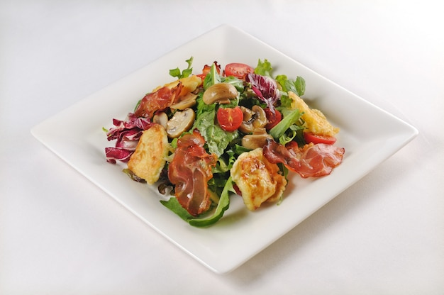 Isolated shot of a plate with salad with chicken and bacon - perfect for a food blog or menu usage