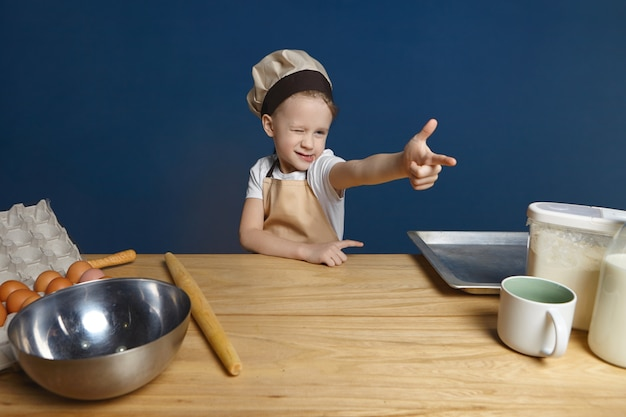 Isolated shot of playful cute male kid in apron and hat winking