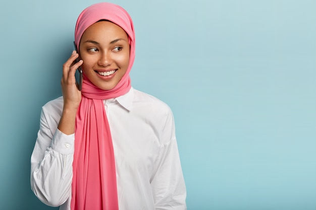 Isolated shot of pleasant looking female model speaks over modern mobile phone, talks with someone, smiles sincerely, focused away, stands against blue wall with empty space, wears muslim clothes