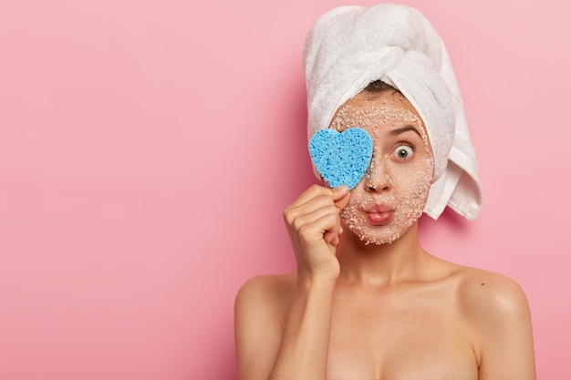 Isolated shot of pleasant looking woman covers eye with sponge, keeps lips rounded, has naked well cared body, bugged eyes, wears white towel, isolated over pink background, blank space aside