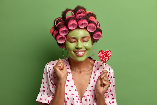 Isolated shot of pleased ethnic female stands with closed eyes, clenches fist joyfully, wears hair curlers, beauty mask, smiles toothily, holds lollipop on stick, dressed in casual domestic clothes
