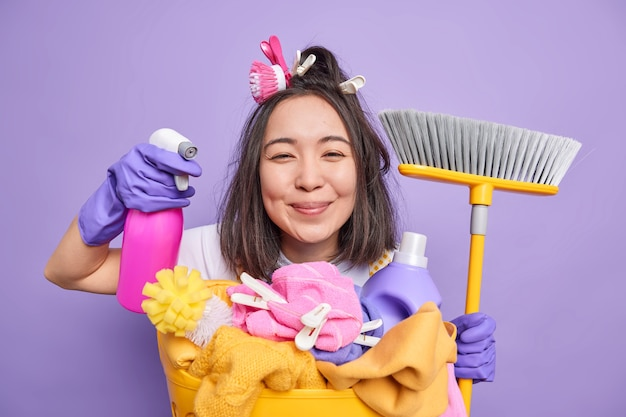 Isolated shot of positive brunette asian housewife holds detergent for cleaning holds broom poses near laundry basket does disinfection of house isolated over purplebackground. cheerful housekeeper