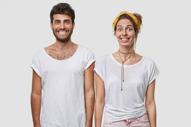 Isolated shot of positive coworkers with funny happy expressions, show white teeth, smile broadly, dressed in casual clothes, pose over  wall, express happiness
