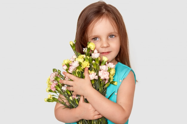 Isolated shot of pretty small girl preapres bouquet of flowers to mum on mothers day, has appealing appearance, dressed in festive clothes, isolated over white wall .spring and children concept