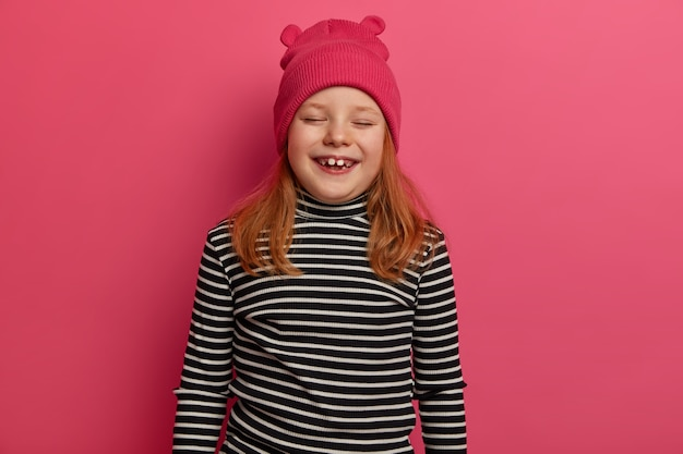 Isolated shot of red haired girl smiles and giggles positively, wears pink hat and striped jumper, being very emotional, comes on birthday party, isolated on pink wall. happy emotions concept