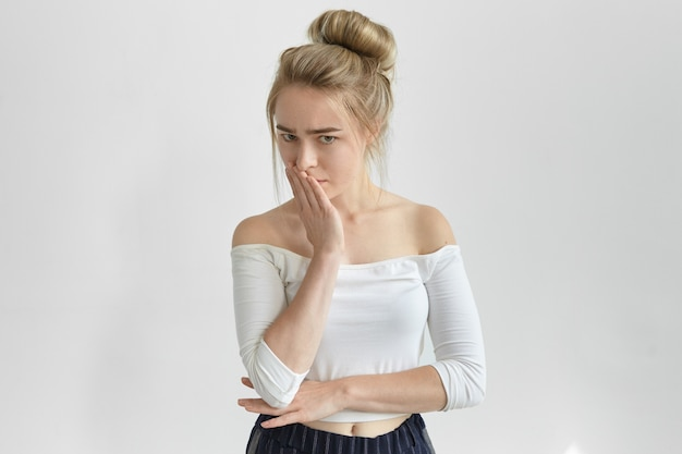 Isolated shot of sad young caucasian woman with hair bun covering mouth, being disappointed or upset with negative news, having frustrated serious facial expression, doesn't know what to do