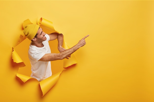 Isolated shot of satisfied male model stands sideways in paper hole, dressed in yellow headgear