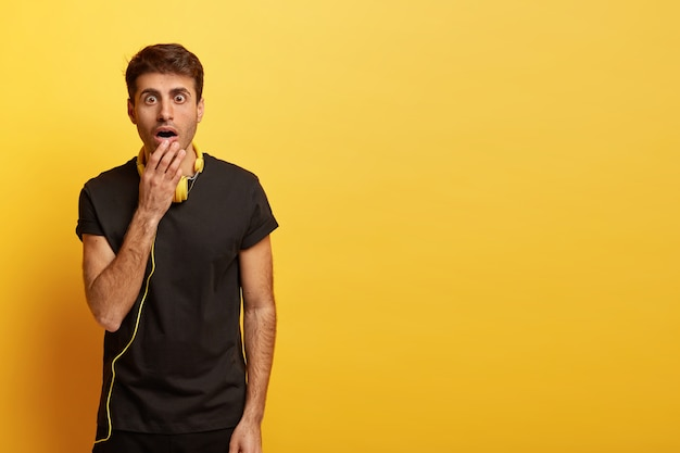 Il colpo isolato dell'uomo caucasico spaventato tiene la bocca ampiamente aperta, vestita di maglietta nera