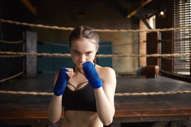 Colpo isolato di auto-determinato fiducioso adolescente ragazza formazione in palestra, tenendo i pugni chiusi davanti a lei
