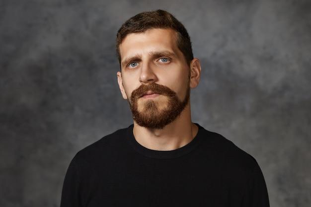 Colpo isolato di serio bello trentenne uomo caucasico con gli occhi azzurri, baffi e folta barba in posa contro il muro bianco, vestito con un maglione nero