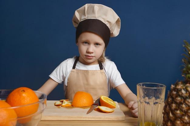 Colpo isolato di chef bambino maschio serio con gli occhi azzurri e capelli biondi, rendendo la frutta fresca o insalata