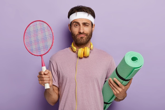 Isolated shot of serious man ready for playing tennis during pastime, holds racket and karemat, listens music