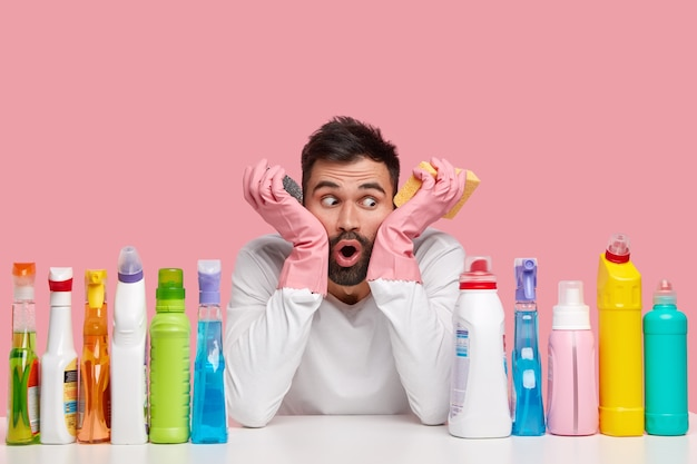 Isolated shot of shocked bearded man looks aside, has frustrated facial expression, wears rubber gloves