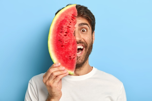 Colpo isolato di uomo sorridente in una giornata estiva in possesso di una fetta di anguria