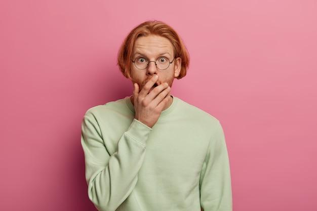 Colpo isolato di uomo hipster dai capelli rossi barbuto stordito copre la bocca aperta, non può credere a notizie scioccanti, vede qualcosa di incredibile, vestito con un maglione casual, posa contro il muro rosa