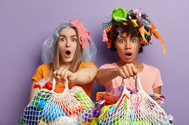 Isolated shot of stunned multiethnic women stare with bugged eyes and surprisement, hold net bags filled with plastic waste, going to recycle reusable litter, stand closely over purple wall